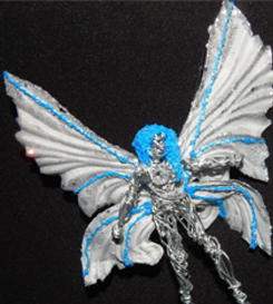 Metal fairy with upcycled floral wings; the blue is filament for the hair and wing decorations.